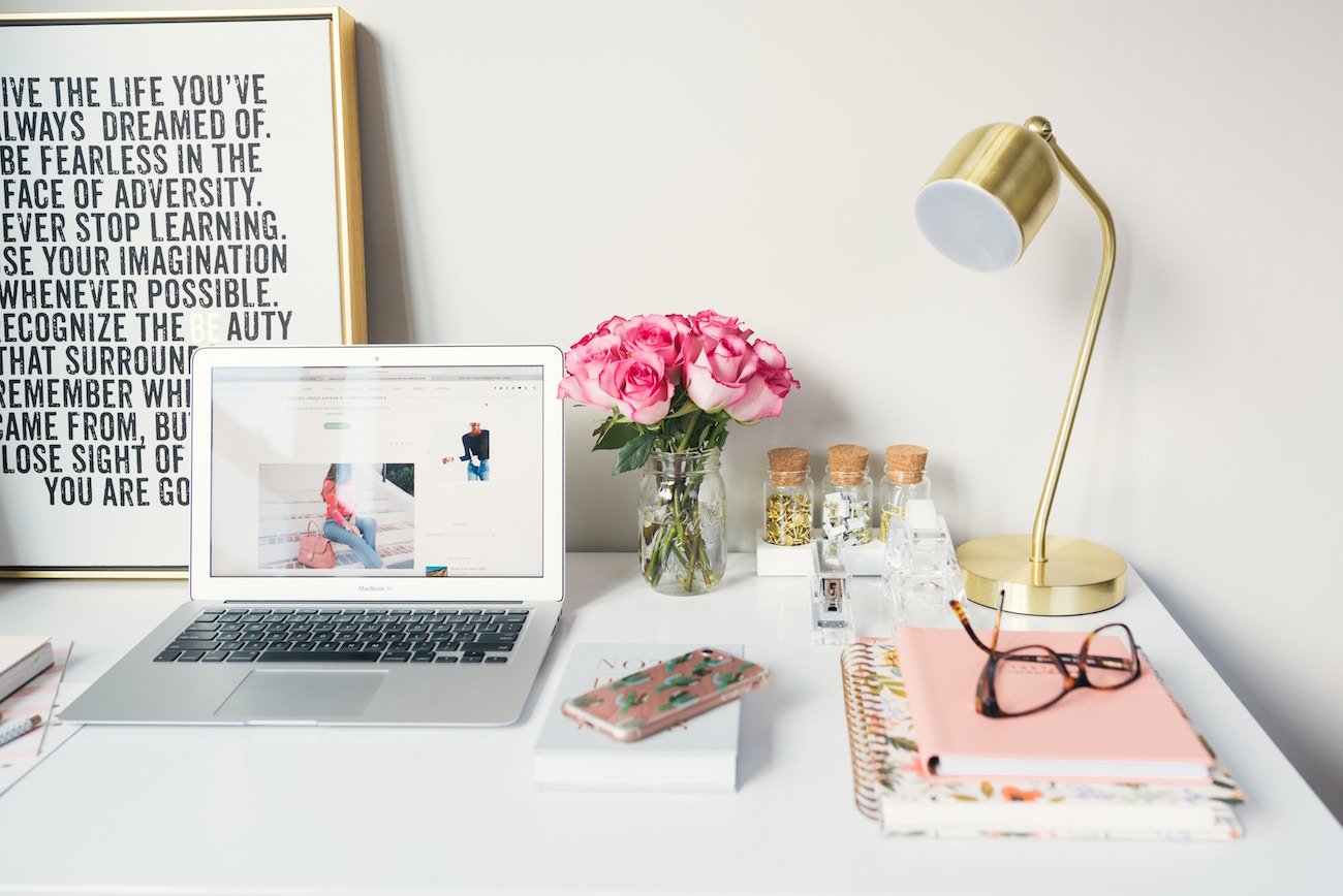 Image of a trendy desk with inspirational quote, laptop, flowers and notebooks